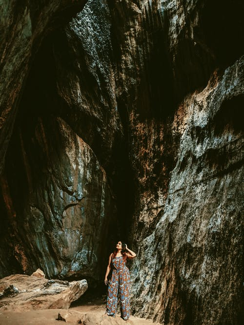 Woman Standing beside rocks