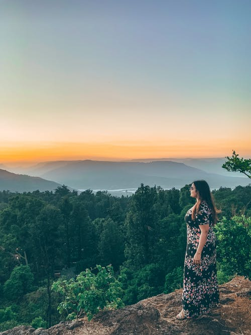 Woman Wearing Dress Standing on Cliff Overlooking Forest and Mountains