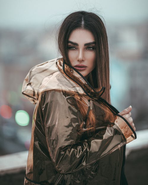 Selective Focus Photo of Woman in Transparent Raincoat Posing While Looking Away