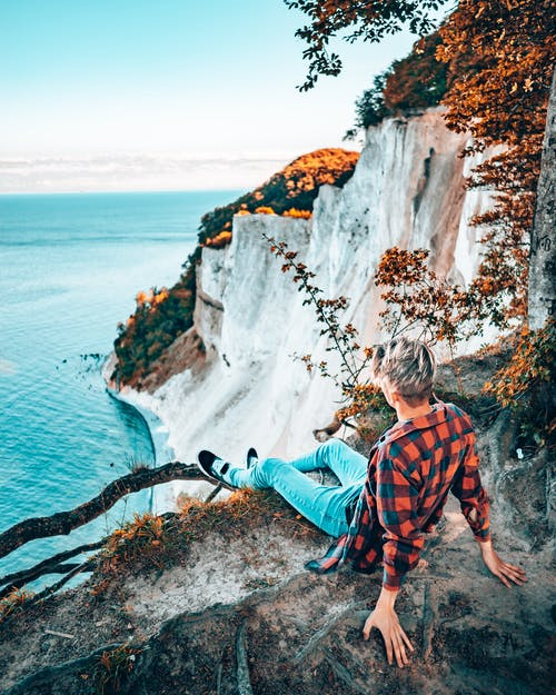 Person Sitting in a Cliff Near Body of Water