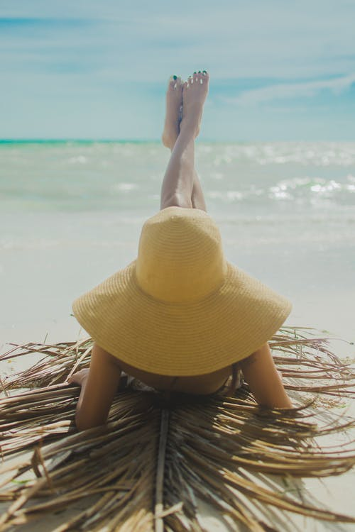 Woman Wearing Yellow Hat With Feet Raised Sunbathing on Shore