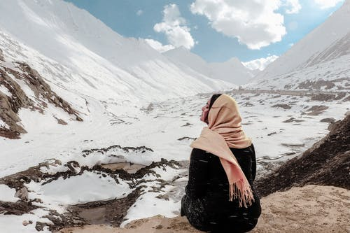 Woman in Black Dress Sitting on Rock at the Valley Covered in Snow