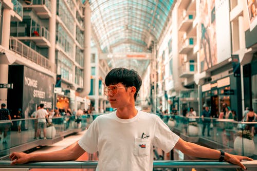 Man in White Crew Neck T-shirt Standing in Mall