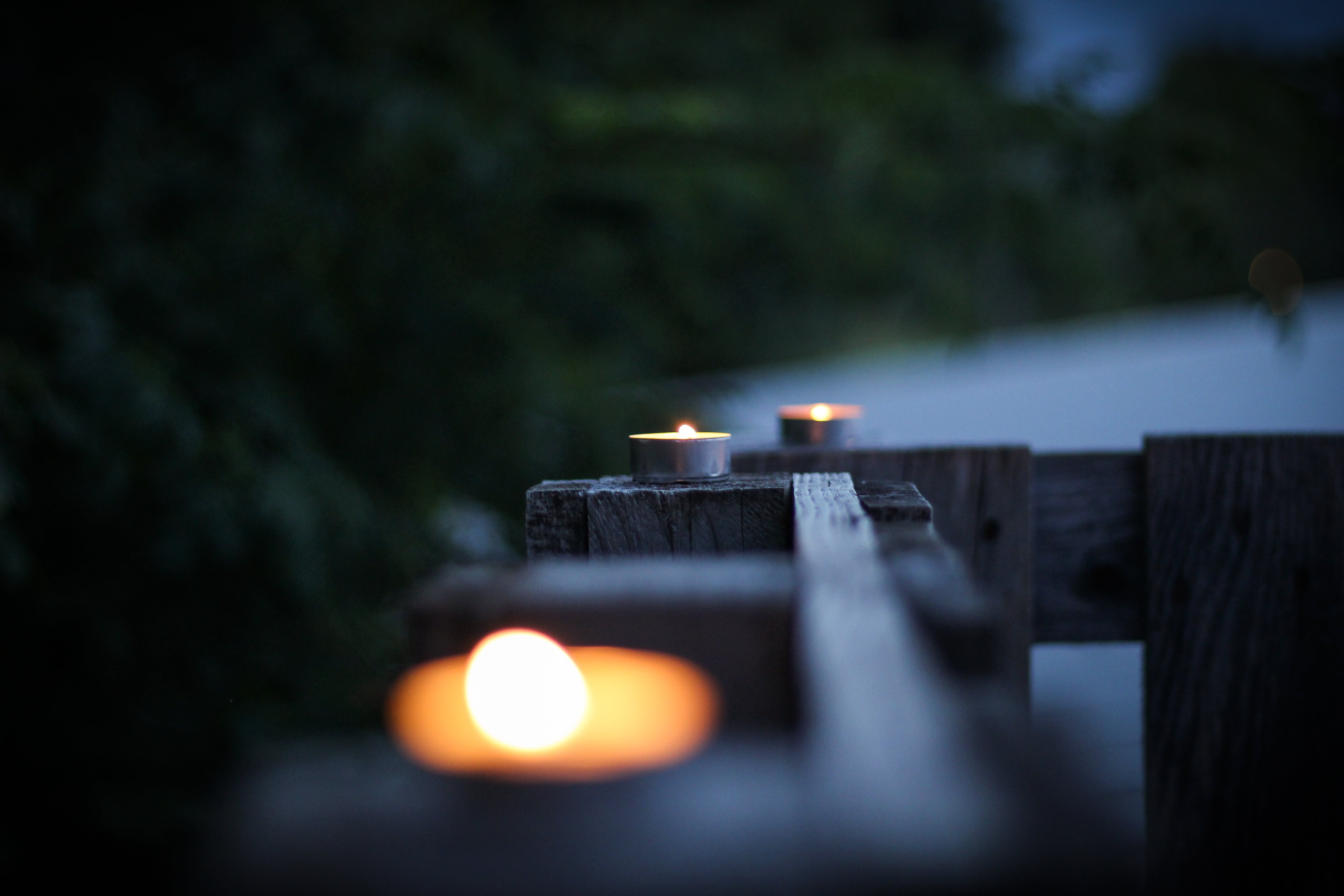 Selective Focus Photo of Three Tealight on Brown Planks