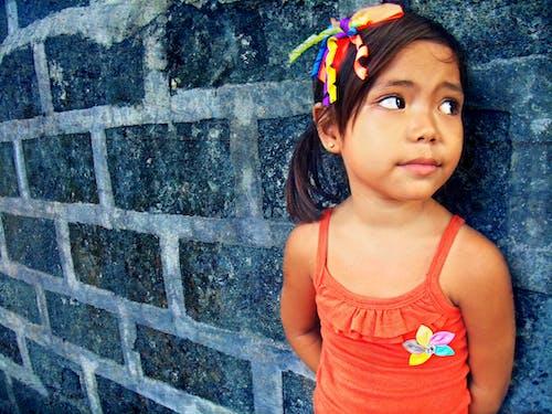 Foto profissional grátis de garotinha, menina na parede, retrato