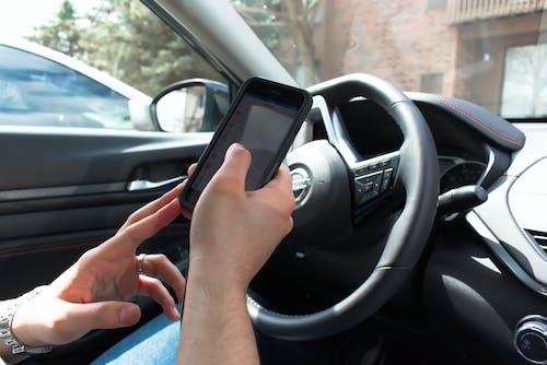 Ingyenes stockfotó autó, autóban, mobiltelefon, mobiltelefon használatával témában