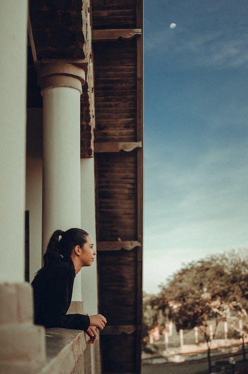 Seitenansicht Foto Der Frau, Die Sich Auf Steingeländer Stützt Und In Die Ferne Schaut