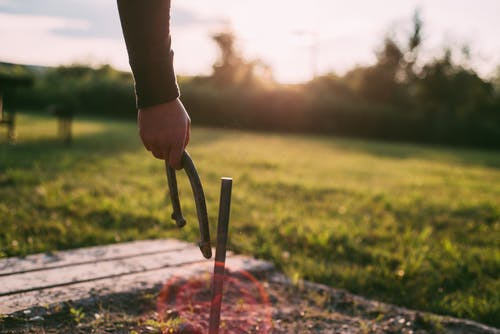 Photo of Person's Hand Holding a Horseshoe Next to Metal Stake in the Ground
