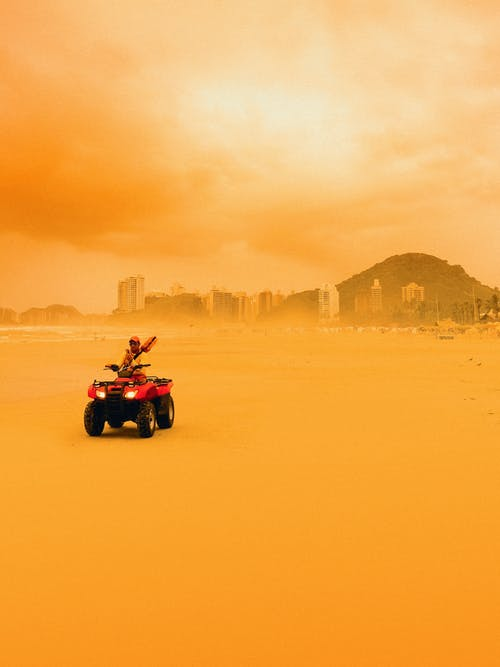 Person Riding Red Atv on Desert