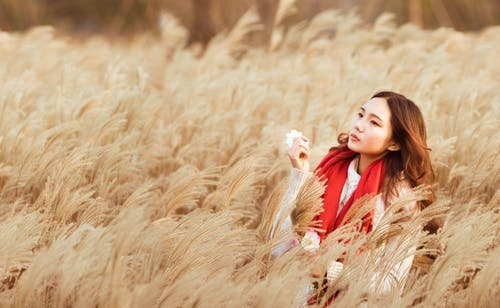 Woman Standing in the Middle of Brown Hay Field