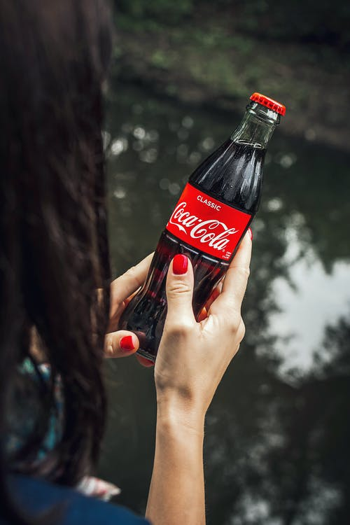 High-Angle Photo of Person Holding a Coca-cola Bottle
