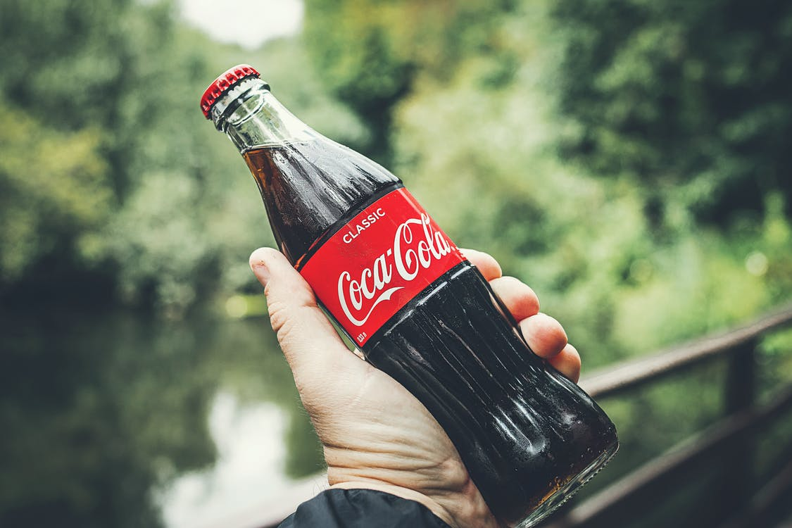 Selective Focus Photography of Person Holding a Coca-cola Bottle