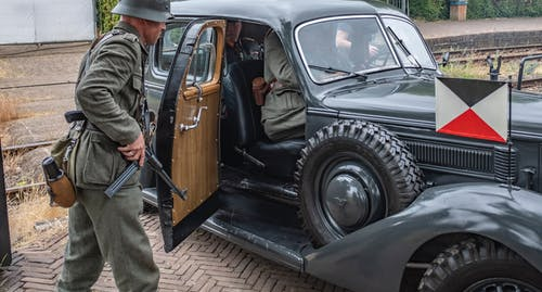 Photo of Man in Old Military Uniform Carrying a Rifle Standing By Vintage Military Car With Soldiers Inside
