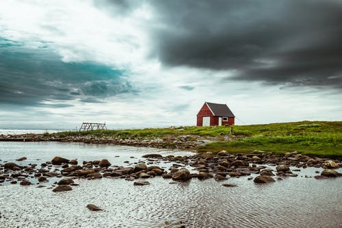 Red and Gray Barn Near Body of Water
