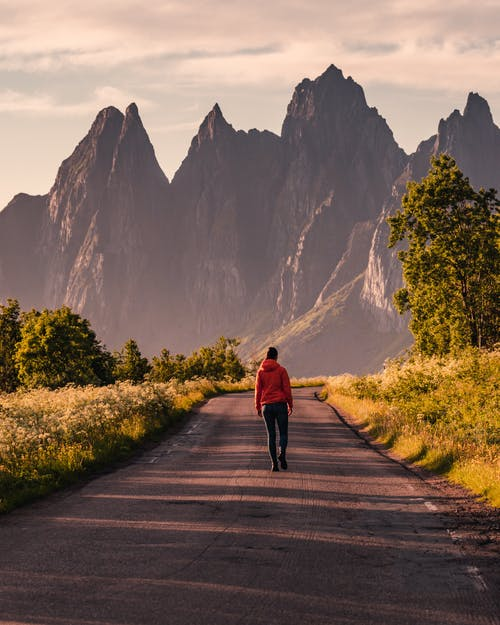 Person in Red Hoodie Walking on Road Towards Mountains