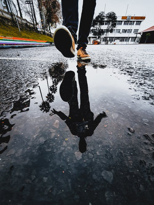 Reflection of a Person Wearing Orange Sneakers