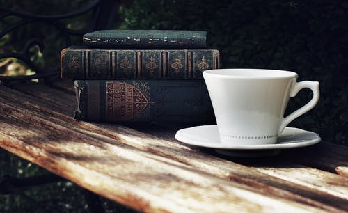 Photo of Ceramic Cup and Saucer Next to a Pile of Books on Wooden Park Bench