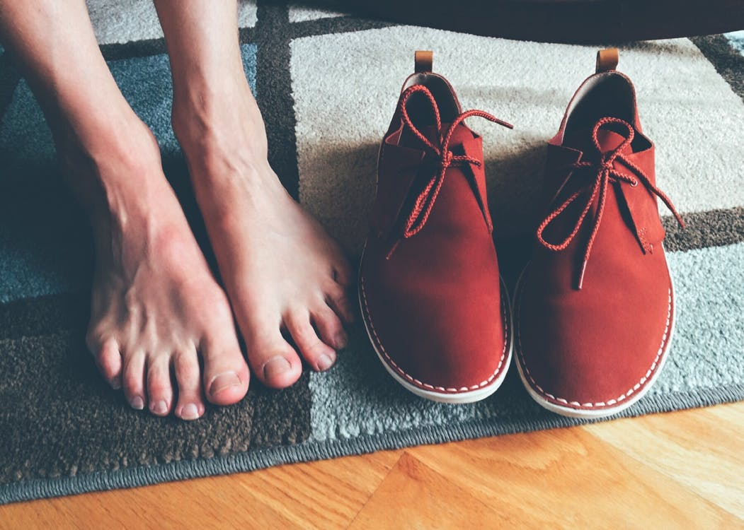 Person's Feet Beside Brown Shoes