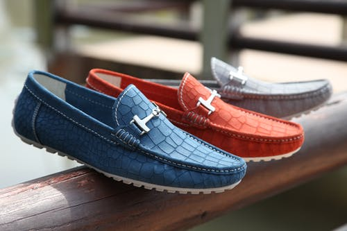 Selective Focus Photography of Three Unpaired Red, Blue, and Gray Leather Horsebit Loafers