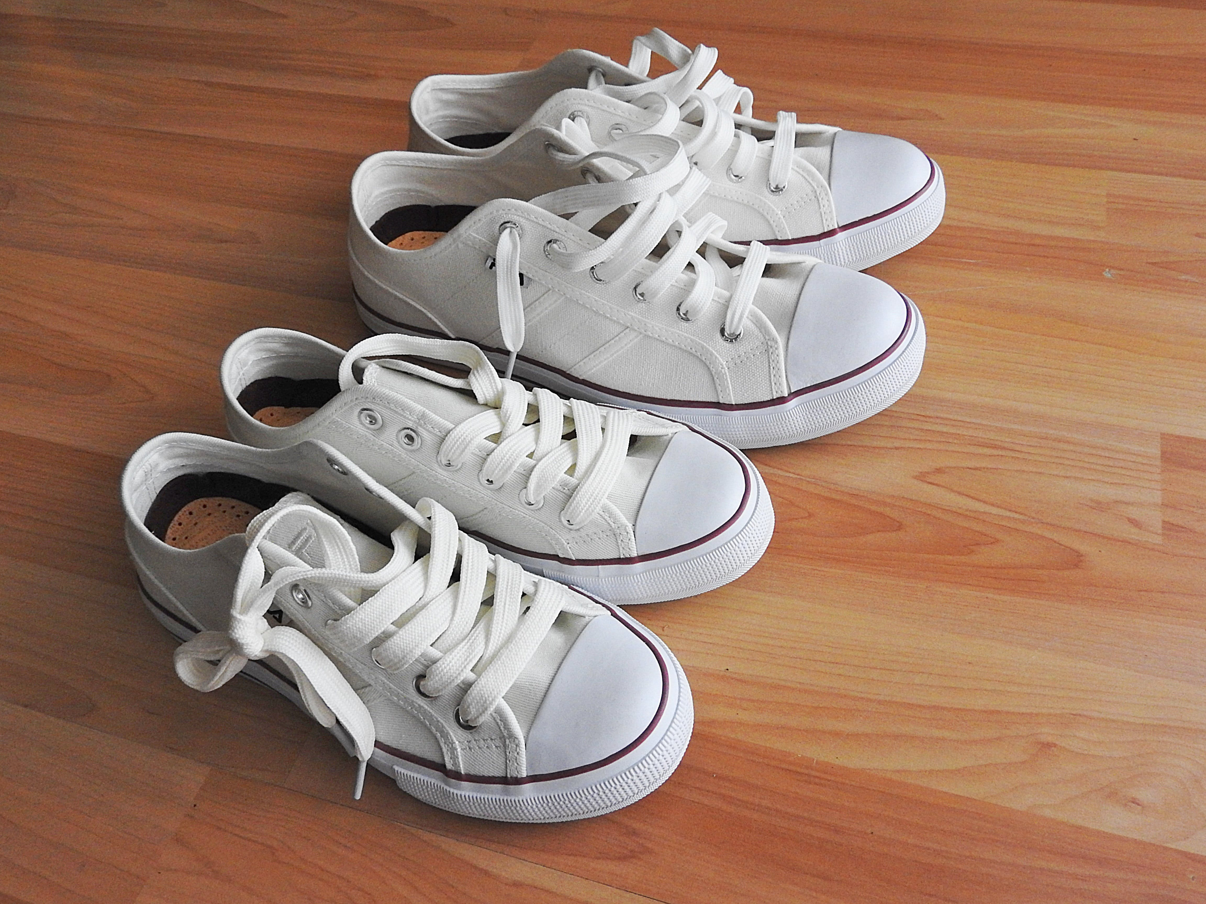 Two Pairs of White Sneakers on Brown Wooden Flooring
