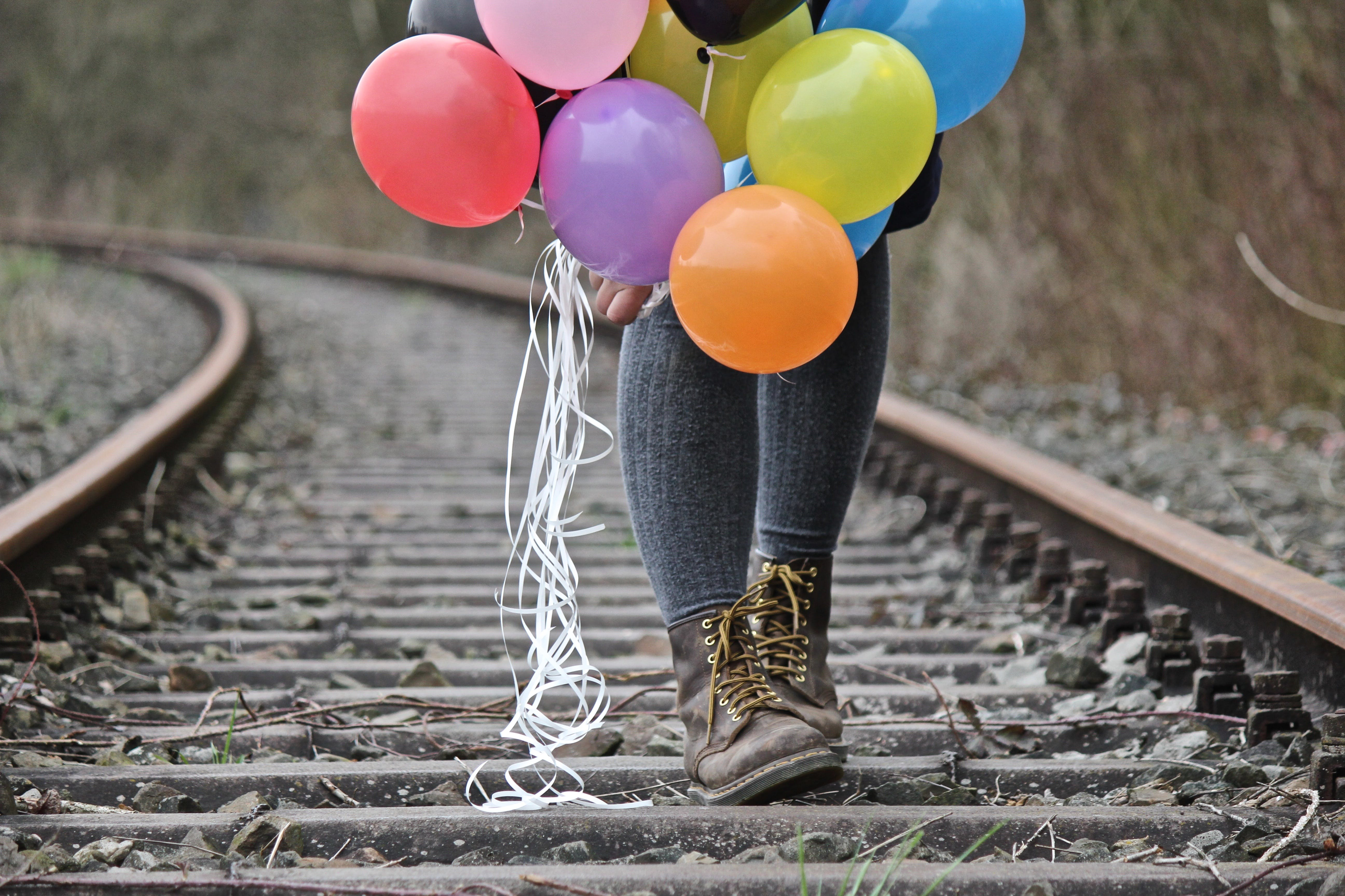 Person Walking on Train Track Holding Balloon
