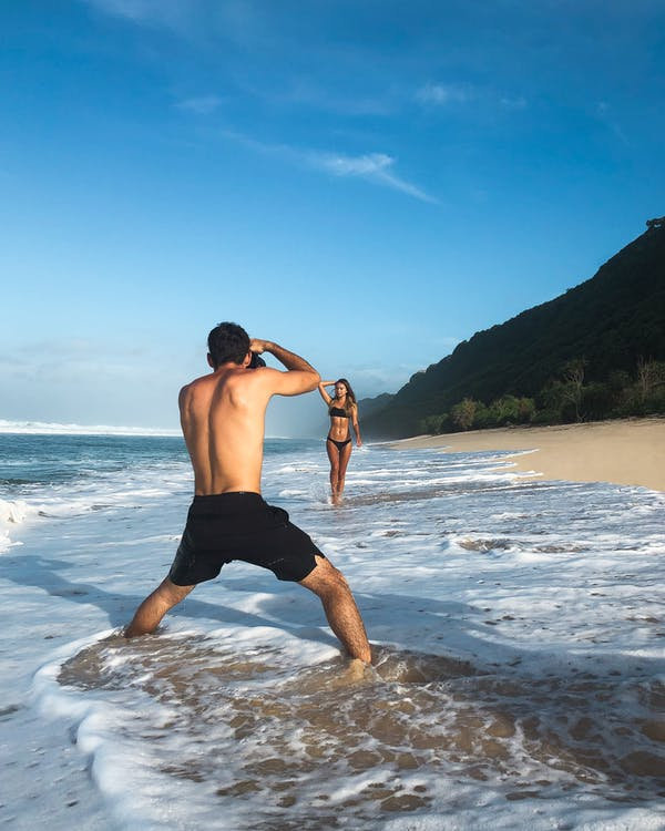 Man Taking Photo of Woman Standing on Shore