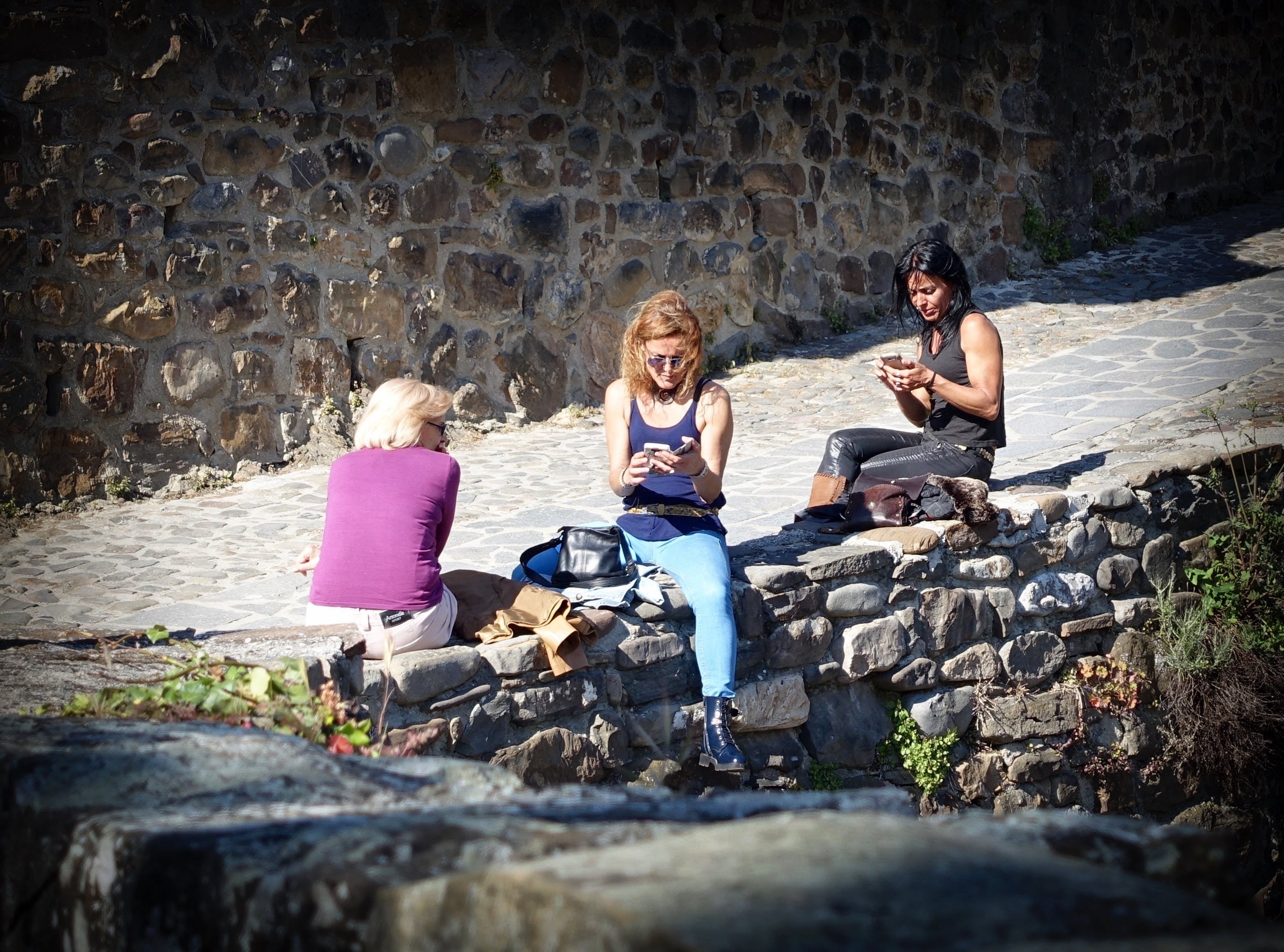Three Women Sitting on Block