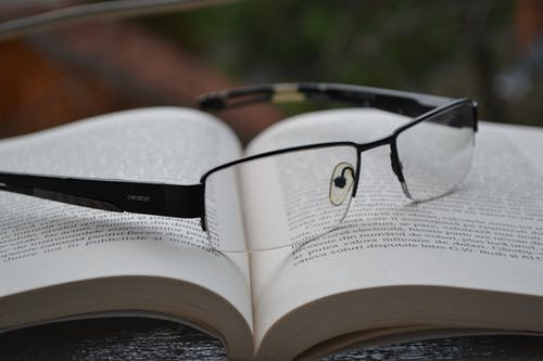 Clear Eyeglasses With Black Frames on Opened Book