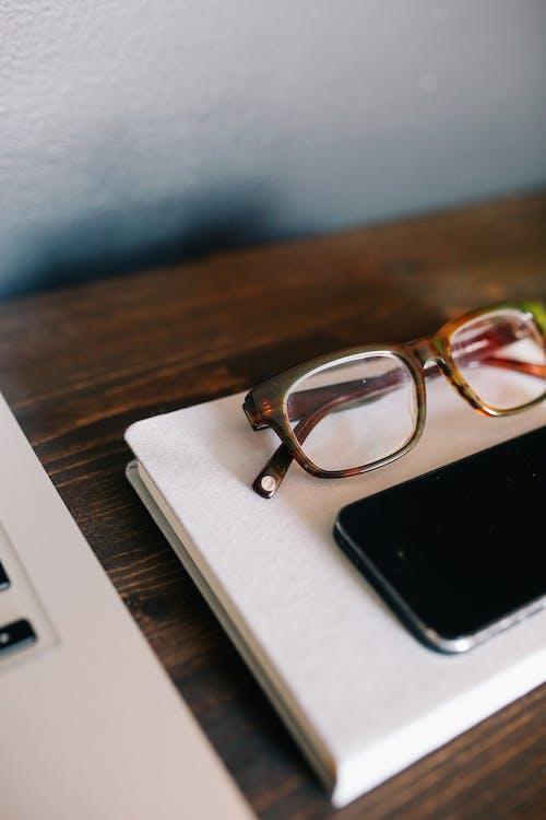 Iphone Beside Eyeglasses on Notebook