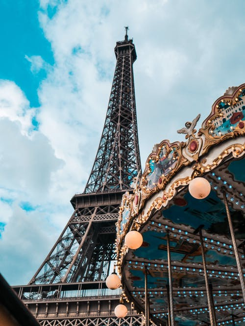 Low angle photography of eiffel tower and carousel