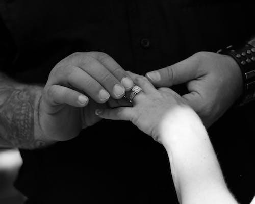 Crop groom putting wedding ring on finger of fiancee