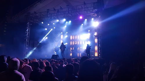 Photo of Band Performing to Crowd of People at a Concert