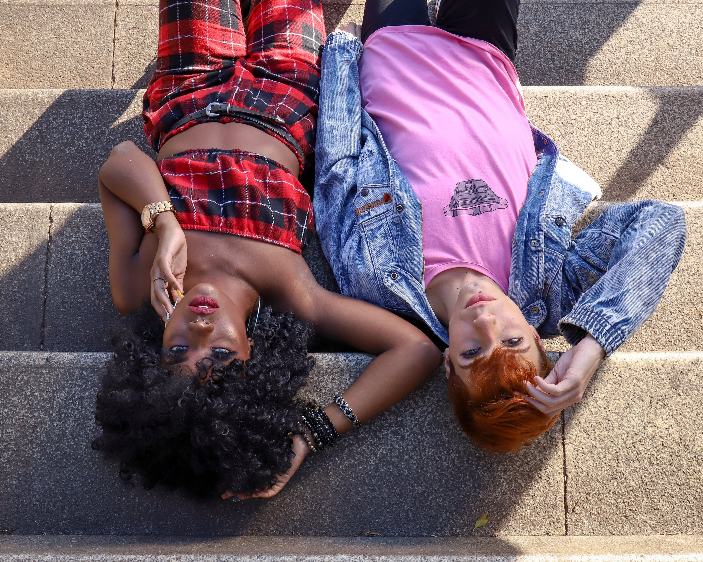 two woman lying on concrete stairs
