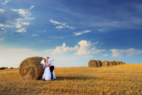 Photo of Couple Kissing Beside Hay Roll