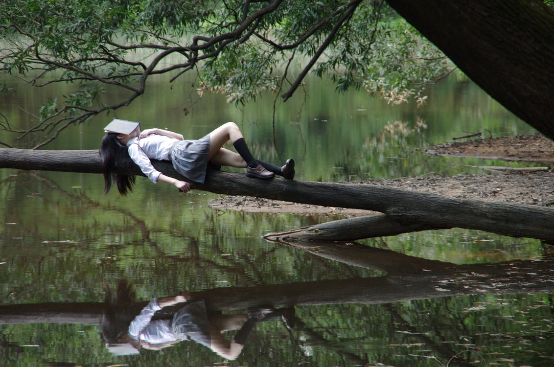 Woman Lying on Tree Near Awter