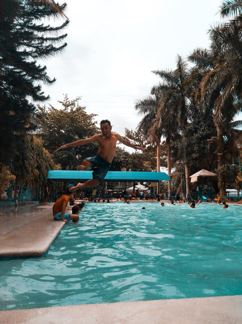 Photo of a man jumping into a swimming pool