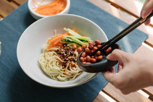 Person Holding Black Chopsticks and White Ceramic Bowl With Noodles