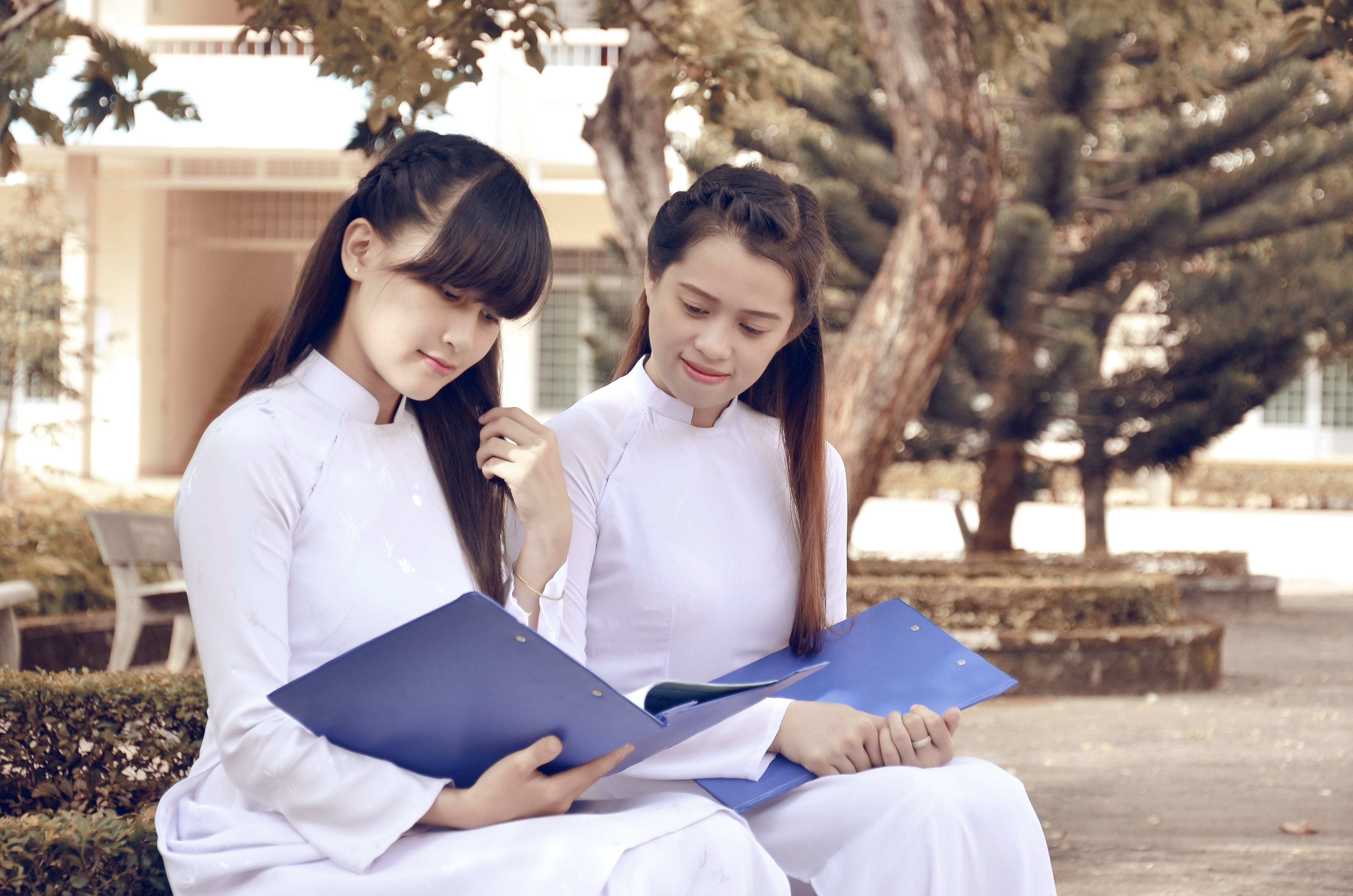 Two Woman Holding Blue Folder
