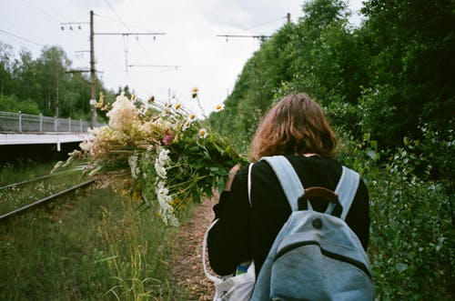 Back view photo of a person wearing a backpack and  holding flowers