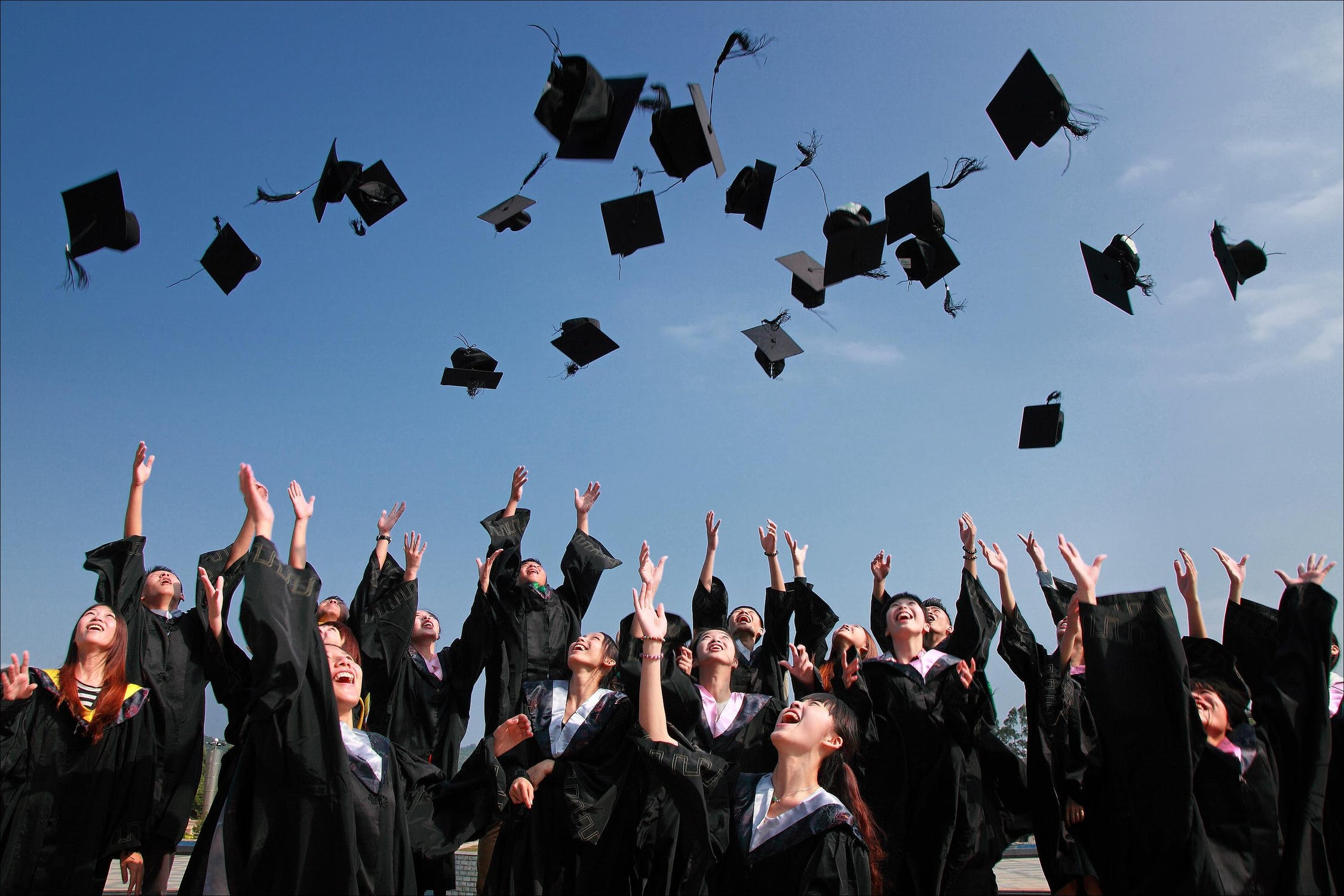 Picture of students throwing graduation caps in the air
