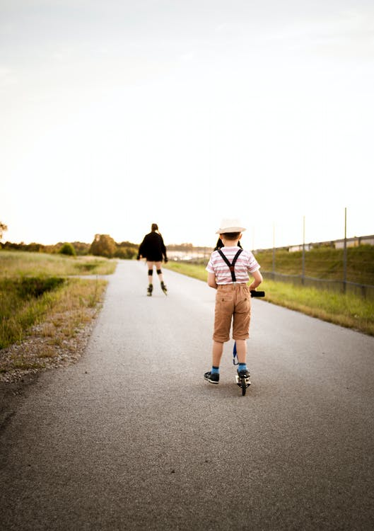Boy Wearing White and Blue Short Riding Kick Scooter