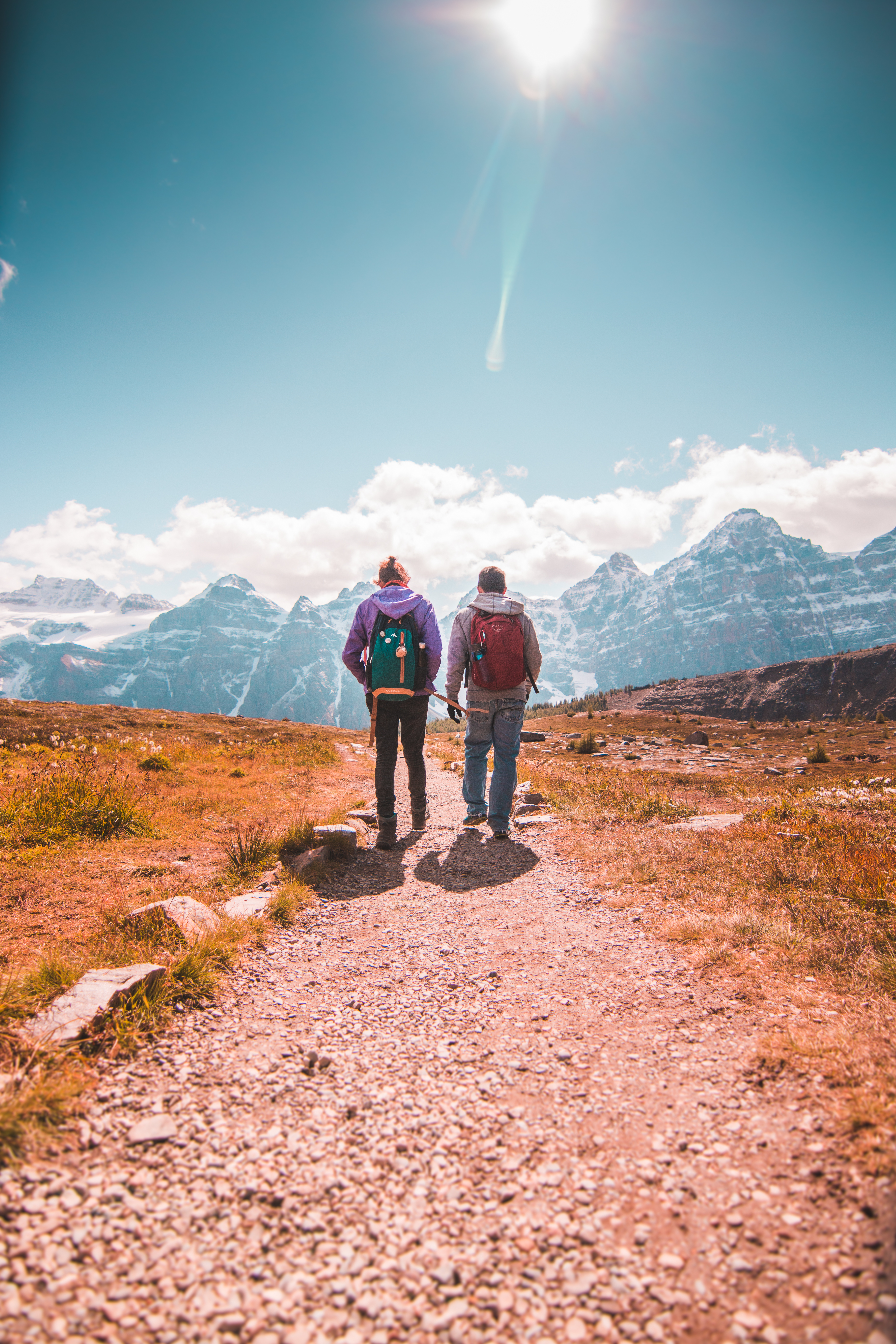 Two Person Walking on Unpaved Road