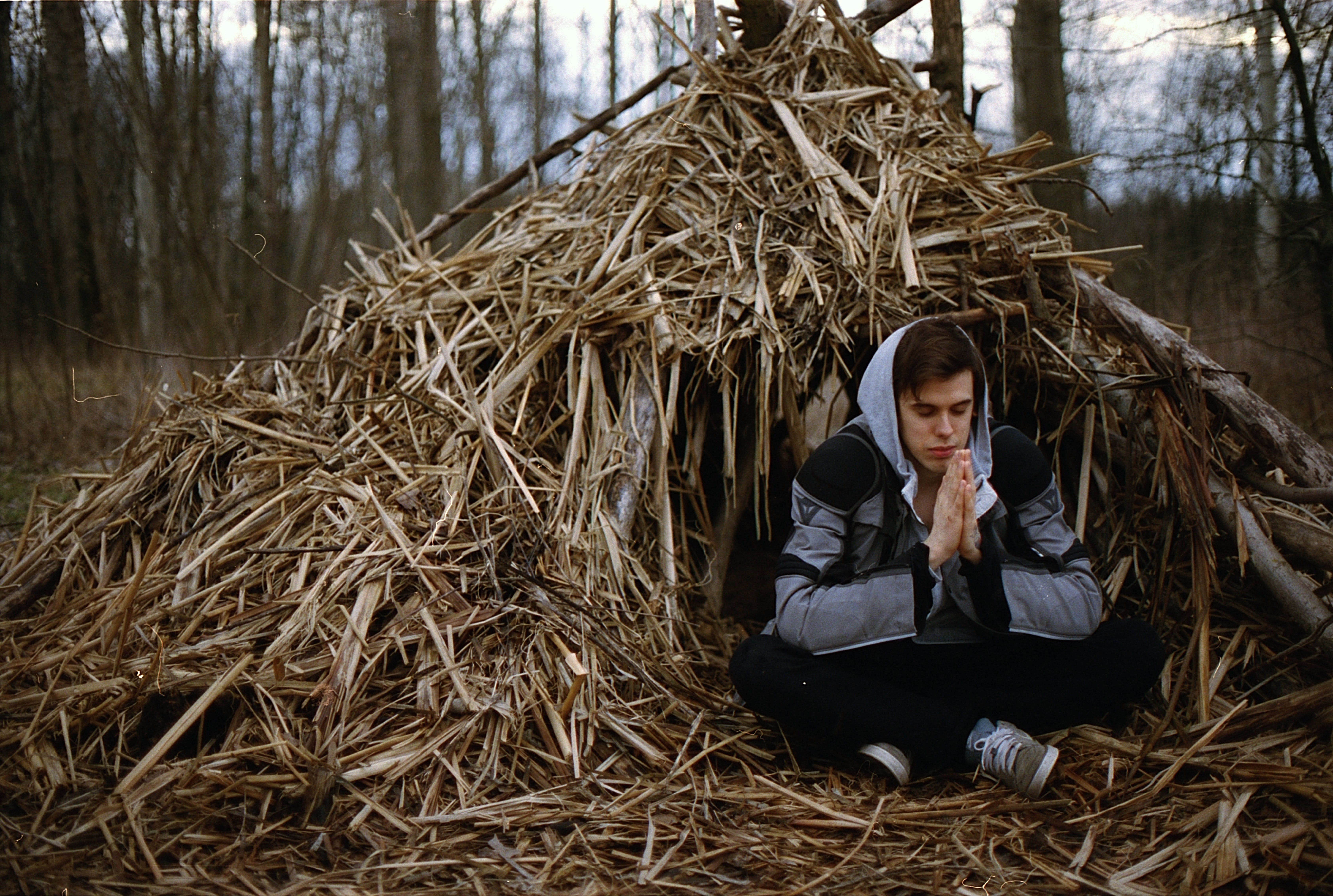 Man Sitting in Front of Hut