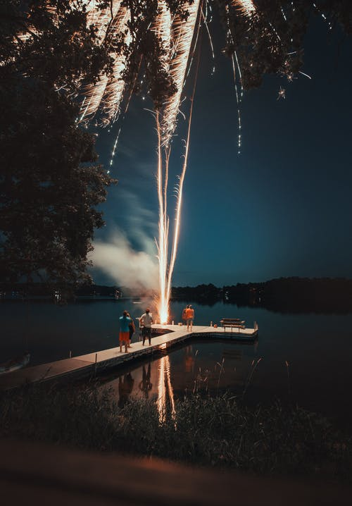 Photo of people standing on white dock watching fireworks during nighttime