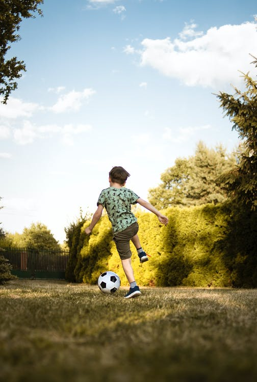 Low-Angle Photo of a Boy Playing Soccer