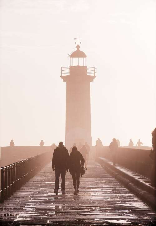 Two People Walking Near Lighthouse