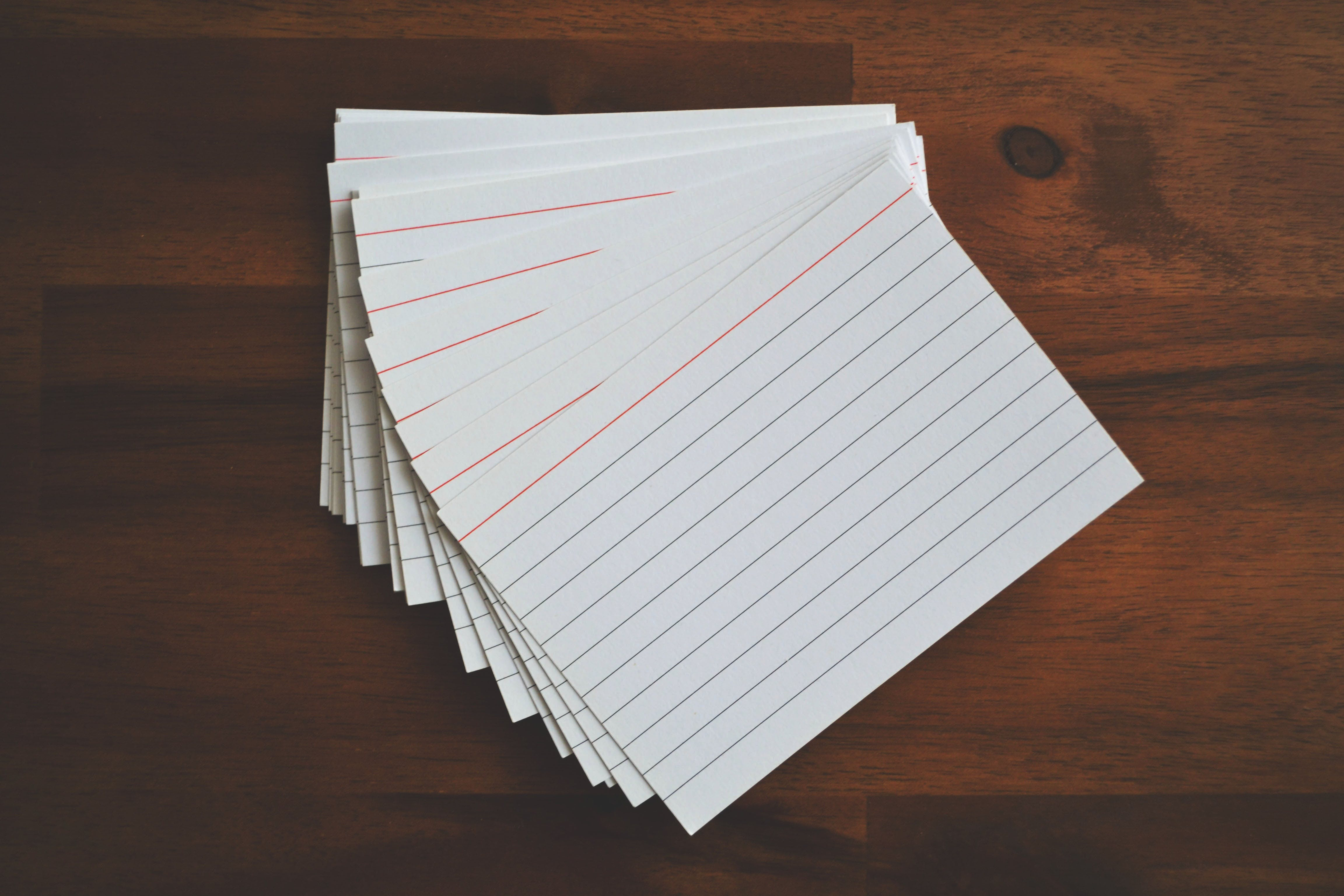 White Ruled Paper Lot on Brown Wooden Surface