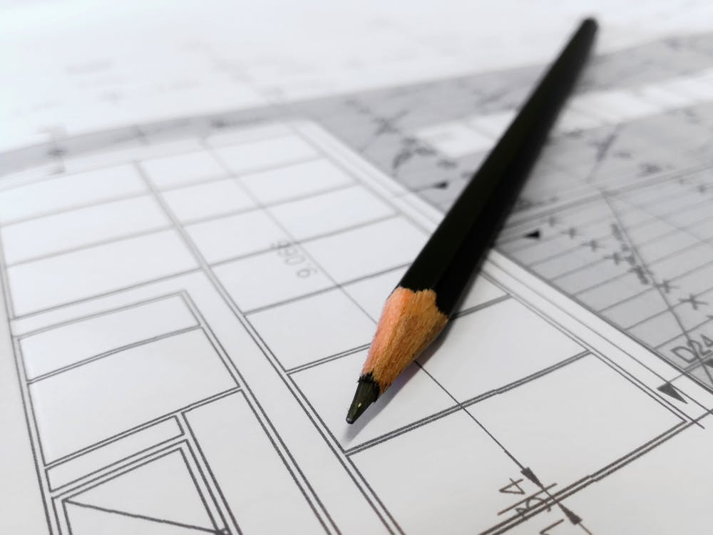 Close-up view of a pencil lying atop architectural plans for a building.
