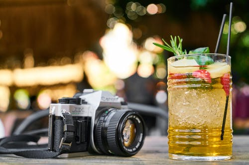Close-Up Photo Of Drink Beside A Camera