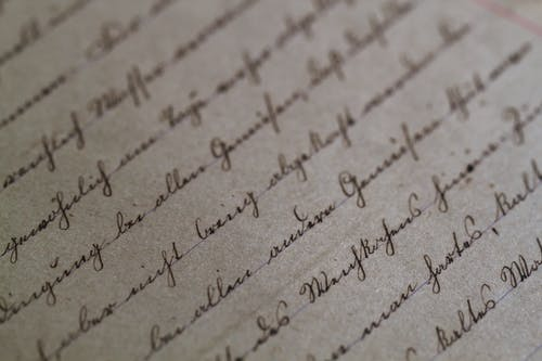 Selective Focus Photo of Gray Paper With Handwritings